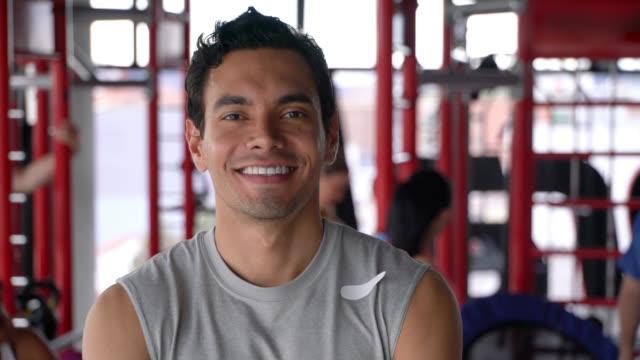 vídeos y material grabado en eventos de stock de foto de la cabeza de entrenador personal en el gimnasio frente a la cámara sonriendo - bien parecido