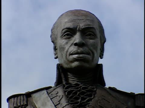 Head shoulders of statue of Haitian Revolutionary leader FrancoisDominique Toussaint L'ouverture ZO WS Statue on pedestal w/ palm fronds FG History...