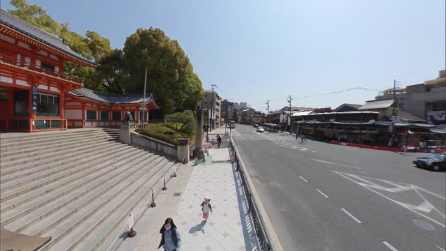 heading south along the higashi-oji-dori road in the city of kyoto with the nishiromon of the yasaka shrine on the left and panning, dolly shot... - shinto shrine stock videos & royalty-free footage