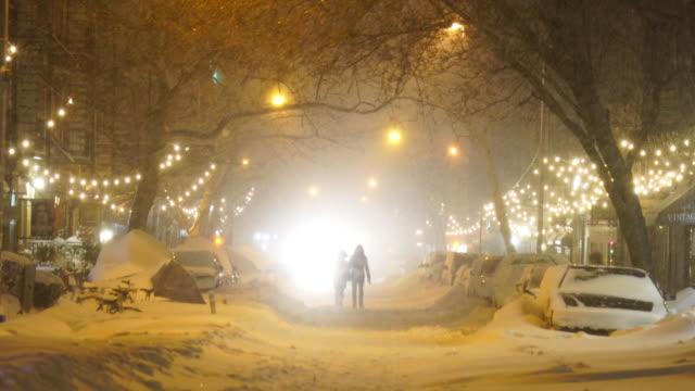 vidéos et rushes de headlight of vehicle illuminates snowy street and people. - phare de véhicule