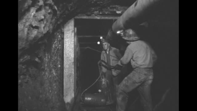vídeos de stock, filmes e b-roll de headlight shines as mine cart emerges from dark tunnel miners ride on cart mine cars are filled with ore which is probably cinnabar / miners spray a... - mercúrio metal