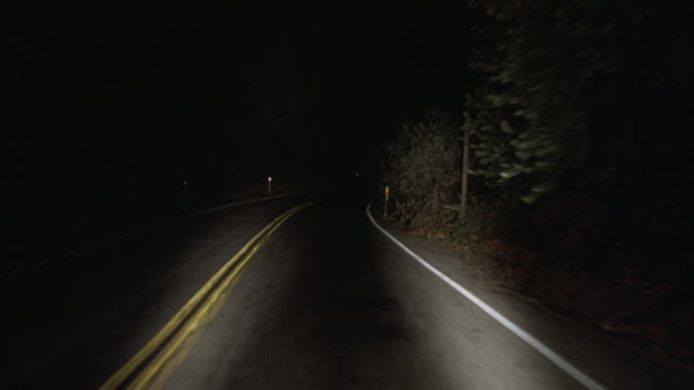 headlights illuminate a deserted country road. - empty road stock videos and b-roll footage