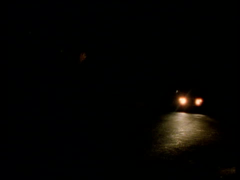 headlights of jeep travelling along dark road pass camera - headlight stock videos and b-roll footage