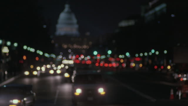 SELECTIVE FOCUS Headlights of traffic on Pennsylvania Avenue, with the U.S. Capitol Building beyond / Washington, D.C., United States