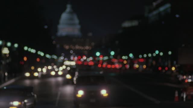 vídeos de stock, filmes e b-roll de selective focus headlights of traffic on pennsylvania avenue, with the u.s. capitol building beyond / washington, d.c., united states - pennsylvania avenue