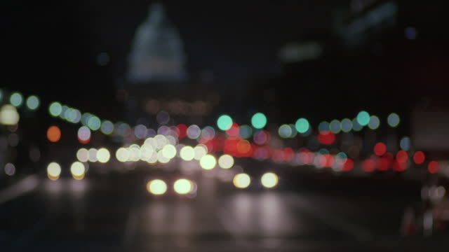 vídeos de stock, filmes e b-roll de selective focus headlights of traffic on pennsylvania avenue, with the u.s. capitol building beyond / washington, d.c., united states - desfocado foco