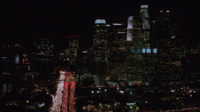 aerial headlights streaming out of illuminated buildings, including the u.s. bank tower at night as commuters leave downtown / los angeles, california, united states - us bank tower stock videos & royalty-free footage