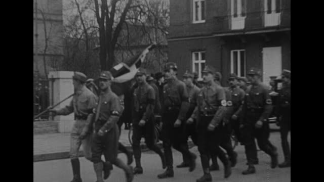headline in sunday morning post nazi newspaper in munich announces victory / small band of sa troops marches in street / ss men outside building / ss... - guarding stock videos & royalty-free footage