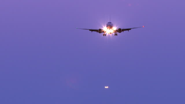 LS head-on view of twin-engine jetliner with bright lights approaching and flying over camera on final approach before landing  / San Diego, California, USA