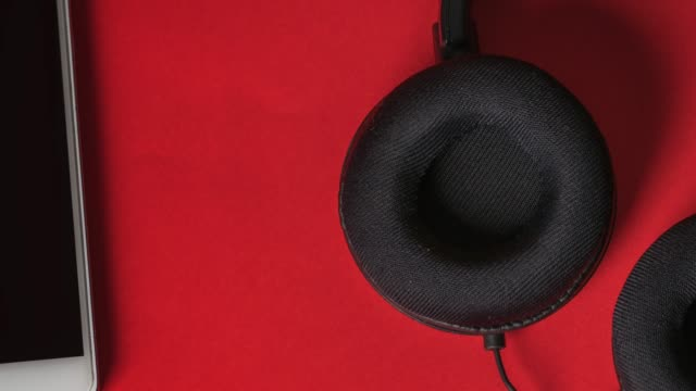 headphones connected to white smartphone on a red background - headphones stock videos & royalty-free footage