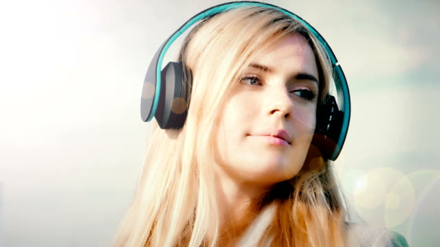 Headphones, music, coffee and sunlight. Blonde woman outdoors.