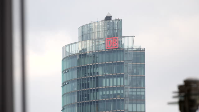 headquarter of the german railway in berlin. the abbreviation db can be seen in red letters on the roof of the building at potsdamer platz in berlin - rail transportation stock videos & royalty-free footage