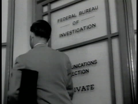 headquarters washington d.c. . man entering building doors. int agent entering 'communications section' office. vs women typing at teletypes. machine... - 1942年点の映像素材/bロール