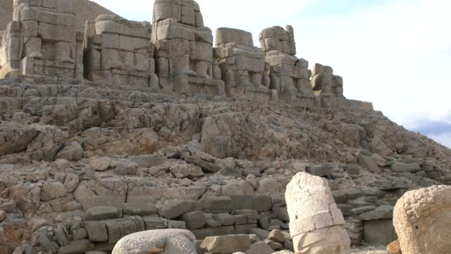 heads and bodies of the statues scattered throughout the the eastern terrace of the mount nemrut (nemrut dağı), southeast turkey - gammal ruin bildbanksvideor och videomaterial från bakom kulisserna