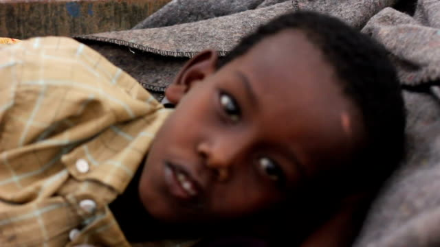 heads home after appointment with doctor at un hospital man carrying sick child inside a wheel barrel on july 30, 2011 in dadaab, kenya - アフリカの角点の映像素材/bロール