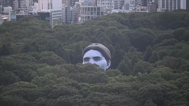 JPN: Giant hot air ballon head peaks over Tokyo trees