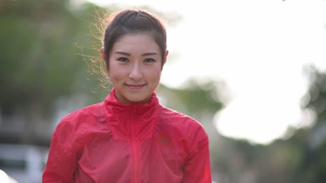 vídeos y material grabado en eventos de stock de disparo a la cabeza asiático atleta chino mirando a la cámara durante la puesta del sol sonriendo - pueblos de asia oriental