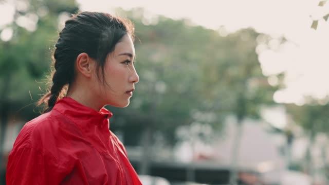 日没の涼しい態度の間に目をそらすヘッドショットアジアの中国の女性アスリート - 努力点の映像素材/bロール