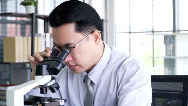vídeos de stock, filmes e b-roll de tiro na cabeça pela dolly tiro: pesquisador médico conduzindo sua experiência em microscópio ótico em seu laboratório - olhando através