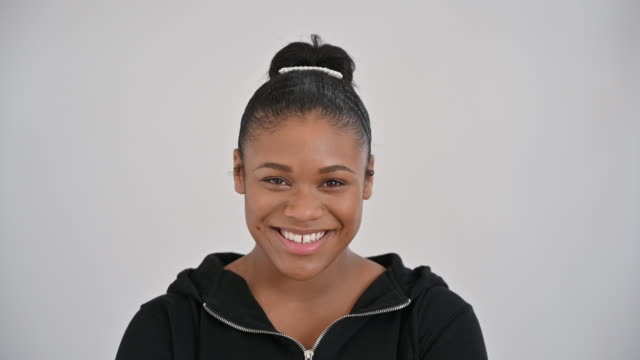 headshot of 19 year old black girl in casual clothing - hair bun stock videos & royalty-free footage
