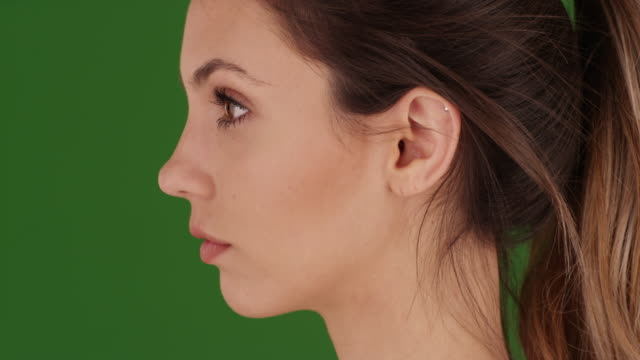 headshot of attractive young woman modeling for green chromakey compositing - profile stock videos & royalty-free footage