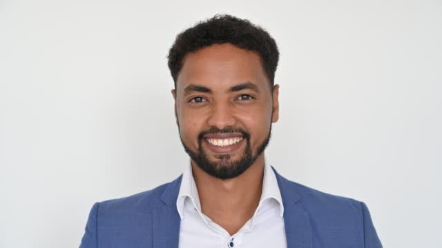headshot of bearded african man in casual businesswear - brown eyes stock videos & royalty-free footage