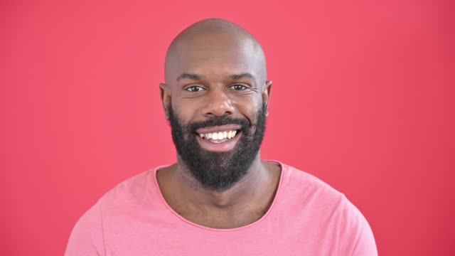 headshot of bearded mid 30s black man wearing pink t-shirt - smiling stock videos & royalty-free footage