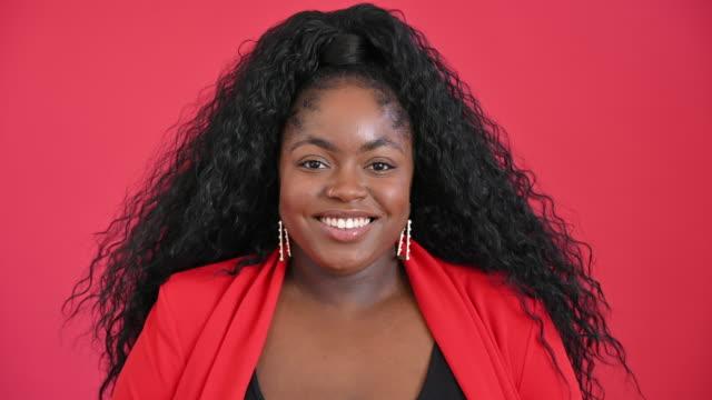 stockvideo's en b-roll-footage met headshot van krullend behaarde jonge zwarte vrouw in rood jasje - lage ronde hals
