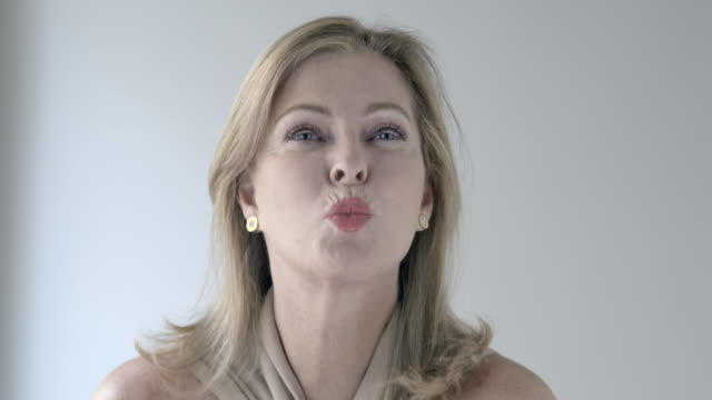 vídeos de stock, filmes e b-roll de headshot of mature blonde woman blowing a kiss to camera - só uma mulher de idade mediana
