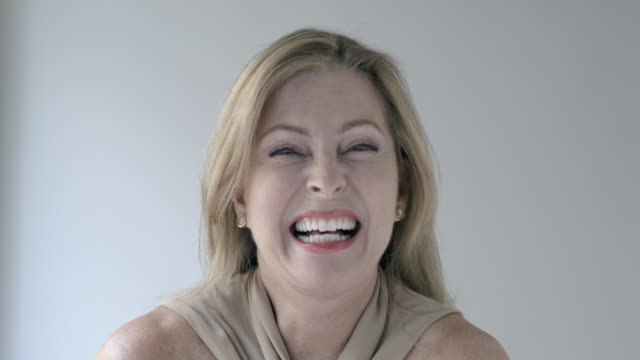 Headshot of mature blonde woman laughing