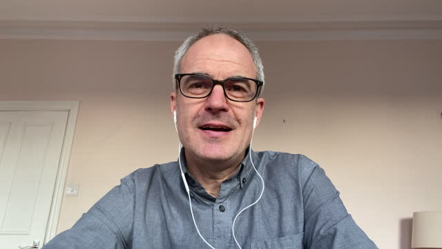 headshot of mature man on video call talking to camera - balding stock videos & royalty-free footage