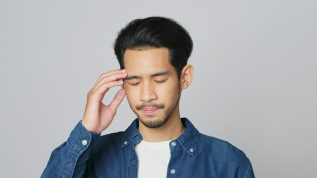 headshot of young asian man in disappointment facial expression while standing over grey background in studio, 4k resolution - guilt stock videos & royalty-free footage