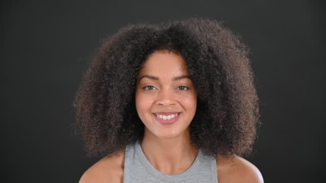 headshot of young black woman with curly hair and casual top - mid length hair stock videos & royalty-free footage