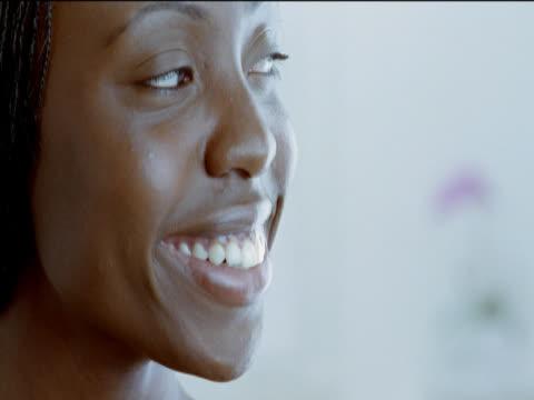 vídeos de stock e filmes b-roll de headshot portrait of a young woman, smiling and looking sideways and then at the camera - olhar de lado