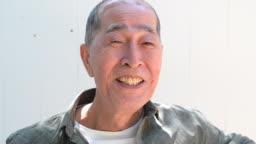 Headshot portrait of senior Japanese man smiling