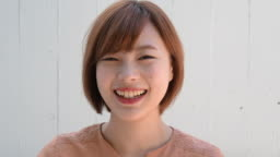 Headshot portrait of young Japanese woman smiling