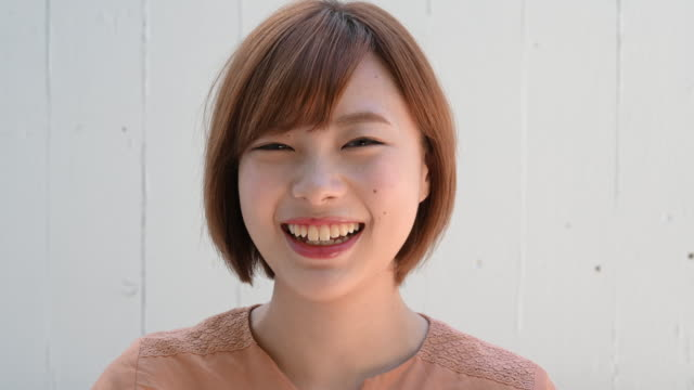 headshot portrait of young japanese woman smiling - japanese ethnicity stock videos & royalty-free footage