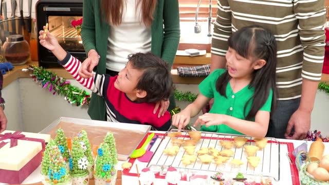 headshot-ansicht: sohn aufgeregt, lebkuchenkeks mit südostasiatischem mehrgenerationen-familientreffen zu großeltern, großvater, großmutter, weihnachtsdessert, lebkuchenkeks, weihnachtsbaum-cupcake in der küche für die weihnachtsfeier vorzubereiten - 35 39 years stock-videos und b-roll-filmmaterial