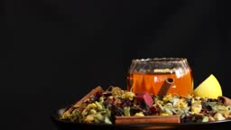 Healing herbs and healthy tea rotating on black background 4