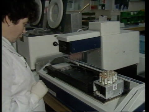 AIDS Testing INT Lab technician watching AIDS testing machine TCMS Machine lowers pipettes onto tray as solution released MS SIDE female technician...