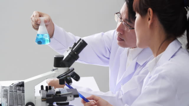 health care researchers working in life science laboratory. young male research scientist preparing and analyzing microscope slides in research lab. - exam stock videos & royalty-free footage