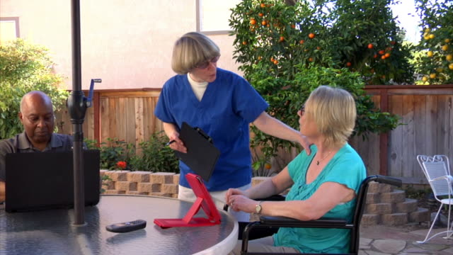 Health care worker on patio with two people