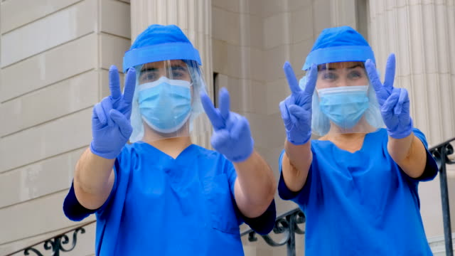 health care workers during a break dancing looking at the camera showing a two fingers victory sign - taking a break stock videos & royalty-free footage