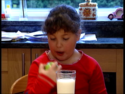 Food Additives warning ENGLAND Two mothers and their children at dining table CMSs Young girls eating apples MS Mother pours glass of milk for...