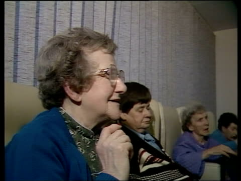housing for the elderly; england, west sussex, horsham 'homelands' home for the elderly tms old ladies seated in lounge r-l tcms old lady listens to... - bericht film und fernsehen stock-videos und b-roll-filmmaterial