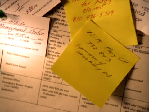Health insurance papers, doctor's appointment cards, and sticky notes spread across a bulletin-board.