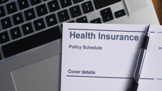 vídeos de stock e filmes b-roll de health insurance schedule with laptop computer - contrato