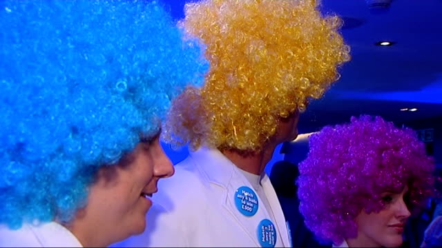 stockvideo's en b-roll-footage met health lottery tickets to go on sale england london int press conference for launch of health lottery people wearing coloured wigs at launch richard... - pruik