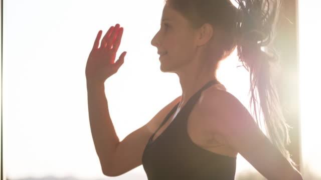 vidéos et rushes de femme de fitness orienté santé faisant des genoux haute en cours d'exécution dans l'exercice de la place - entraînement cardiovasculaire