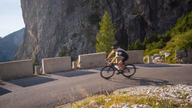 stockvideo's en b-roll-footage met gezondheid georiënteerde wegfietser die bergafwaarts een kronkelende bergweg berijdt, die in een draai gaat - sunny
